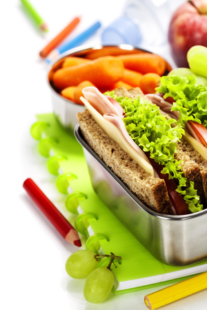 dinnertime: School lunch with a  ham sandwich, apple, grapes and textbooks  Stock Photo