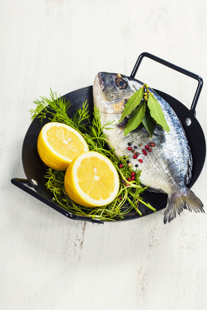saltwater fish: fresh dorado fish and vegetables on wooden board - food and drink