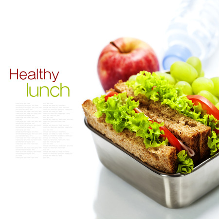 dinnertime: Lunch box with sandwiches, fruits  and water on white background Stock Photo