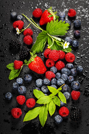 Fresh Berries on Dark Background. Strawberries, Raspberries and  Blueberries.  Health, Diet, Gardening, Harvest Concept photo