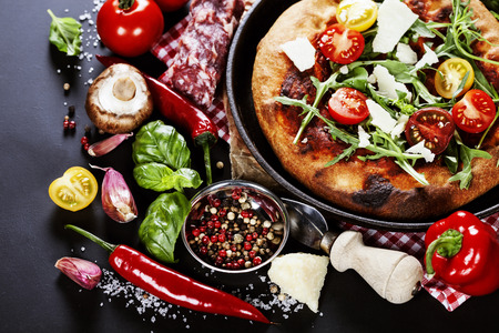 pizza and fresh italian ingredients on a dark background photo