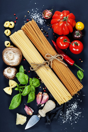 Italian ingredients - pasta, vegetables, spices, cheese - on dark background photo