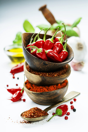 Red Hot Chili Peppers with herbs and spices over white background - cooking or spicy food concept
