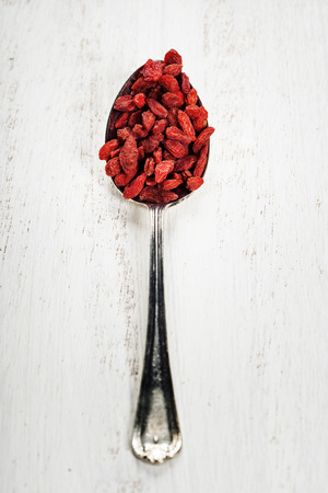 Metal tablespoon of dried goji berries on wooden background photo