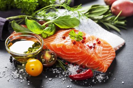 Parte deliciosa del filete de salmón fresco con hierbas aromáticas, especias y verduras - comida sana, la dieta o el concepto de cocina Foto de archivo