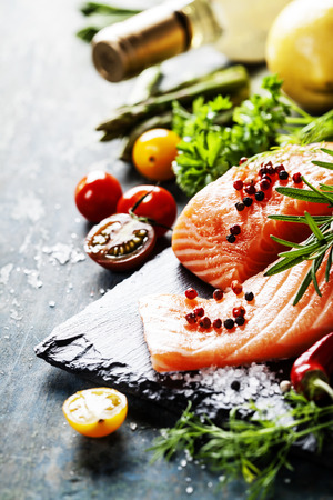 fish oil: Delicious  portion of fresh salmon fillet  with aromatic herbs, spices and vegetables - healthy food, diet or cooking concept Stock Photo