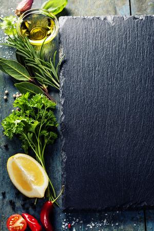 ハーブ、スパイス、オリーブ オイル、塩、レモン、野菜と食品の背景。スレートと木の背景。