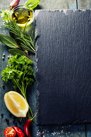 gourmet: Food background, with herbs, spices, olive oil, salt, lemons and vegetables. Slate and wood background.