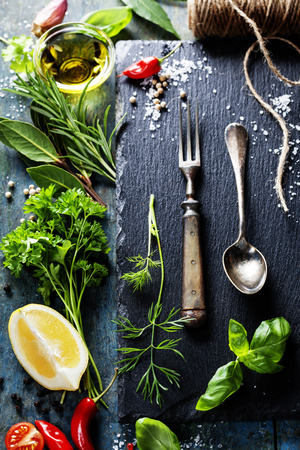 slate: Food background, with herbs, spices, olive oil, salt, lemons and vegetables. Slate and wood background.