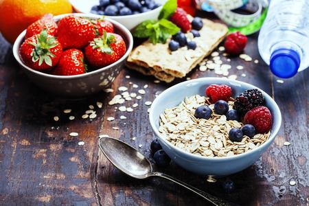 comidas saludables: desayuno dieta - tazones de hojuela de avena, bayas y leche fresca en el fondo de madera - la salud y el concepto de dieta Foto de archivo