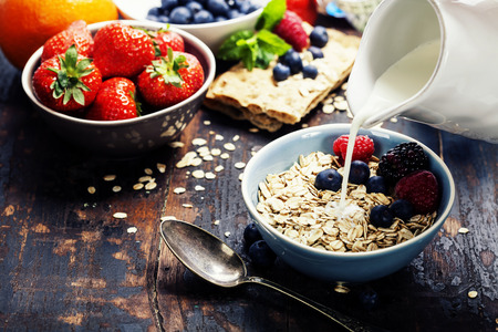 groat: diet breakfast - bowls of oat flake, berries and fresh milk on wooden background - health and diet concept  Stock Photo