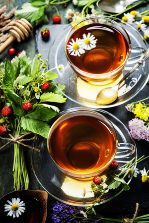 Herbal tea with honey, wild berry and flowers on wooden background  photo