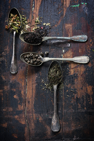 tea spoon: Various kinds of tea (black, green and herbal) on wooden background