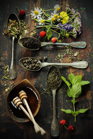 wild mint: Various kinds of tea  with honey, wild berry and flowers on wooden background Stock Photo