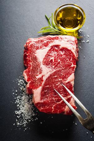 다크 슬레이트 배경에 고기 포크와 원시 쇠고기 스테이크