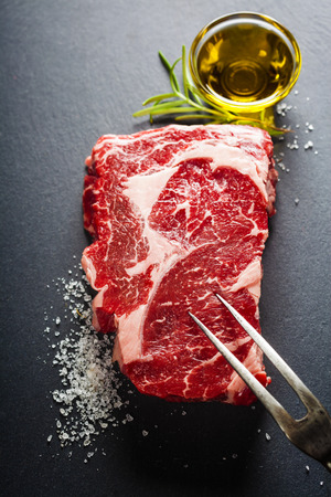 dark meat: Raw beef steak with meat fork on a dark slate background