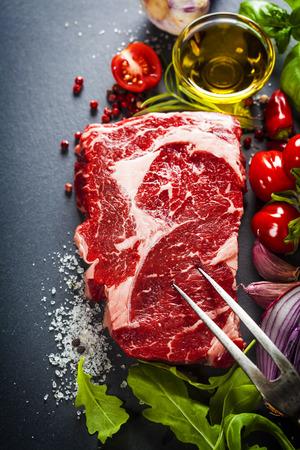 다크 슬레이트 배경에 고기 포크와 재료 원시 쇠고기 스테이크