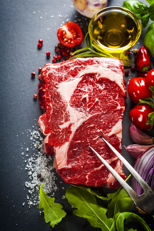 raw beef: Raw beef steak with meat fork and ingredients on a dark slate background Stock Photo