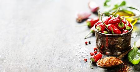 Red Hot Chili Peppers met kruiden en specerijen op houten achtergrond - koken of gekruid eten begrip