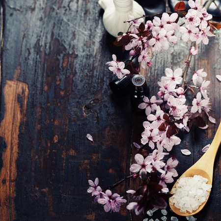 spa therapy: Spa setting with cherry blossoms  over wooden background