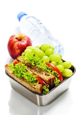 Lunch box with sandwiches, fruits  and water on white background Stock Photo