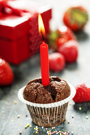 cupcake with candle on wooden board