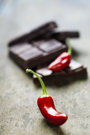 Dark chocolate with chili pepper over wooden background photo