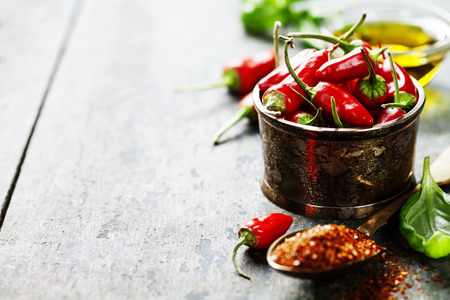 spicy peppers: Red Hot Chili Peppers with herbs and spices over wooden background - cooking or spicy food concept Stock Photo
