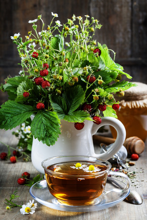 wild mint: bouquet of wild strawberry with herbal tea and honey - bio food or health concept