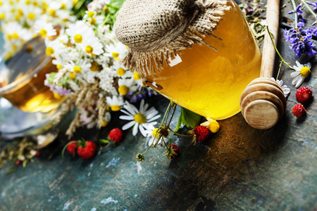 Honey and Herbal tea on wooden background - summer, health and organic food concept photo