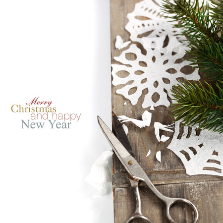 Snowflakes  made of paper and christmas tree on wooden background photo
