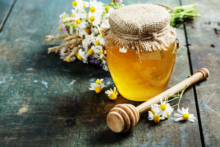 Honey jar and dipper on wooden background Stock Photo
