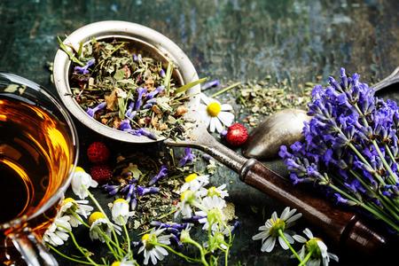 Té de hierbas con flores silvestres y bayas en el fondo de madera - los alimentos bio, la salud y el concepto de dieta Foto de archivo