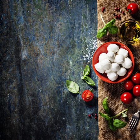 cuisine: Cherry tomatoes, basil leaves, mozzarella cheese and olive oil for caprese salad. Lots of copy space Stock Photo