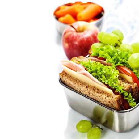 niños sanos: Caja de almuerzo con sándwich, fruta y agua sobre fondo blanco Foto de archivo