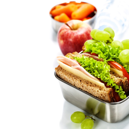 Lunch box with sandwich, fruits and water on white background Stock Photo