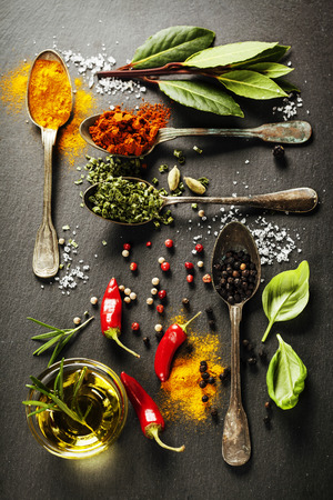 overhead view: Herbs and spices selection - herbs and spices, old metal spoons and slate background - cooking, healthy eating Stock Photo