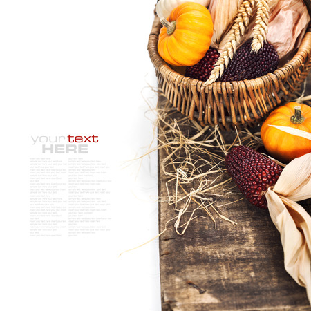 Autumn composition ( pumpkins and corn on old wooden table). Thanksgiving day concept (with easy removable sample text) photo