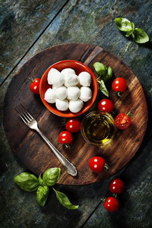 caprese salad: Cherry tomatoes, basil leaves, mozzarella cheese and olive oil for caprese salad. Lots of copy space Stock Photo