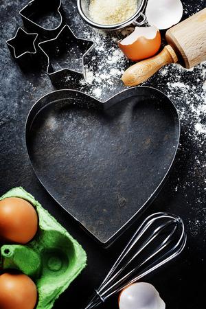 weihnachtskuchen: B�ckerei Hintergrund mit rohen Eiern, Nudelholz, Mehl und Herzform Ausstecher