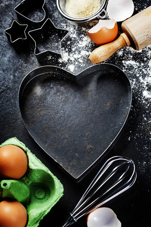 christmas cake: baking background with raw eggs, rolling pin, flour and heart shape cookie cutter