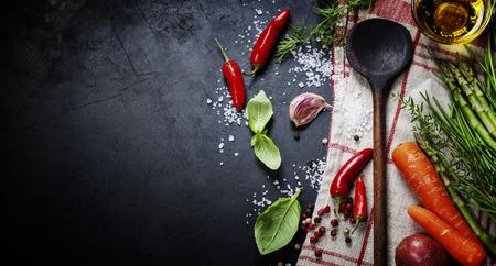 cocinando: Cuchara de madera y los ingredientes en el fondo oscuro.