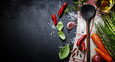 food table: Wooden spoon and ingredients on dark background.