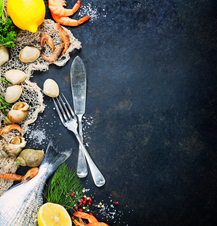 Delicious fresh fish and seafood on dark vintage background.  Imagens