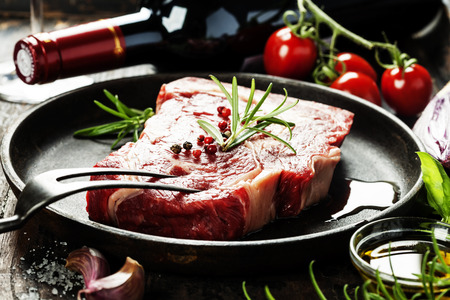 Marbled beef steak in a frying pan with a bottle of wine and vegetables on old wood background