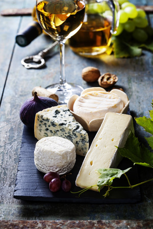 Various types of cheese and white wine on wooden background Imagens