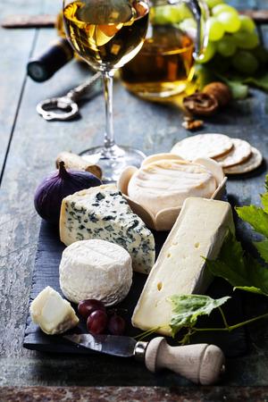 さまざまな種類の木製の背景の上にチーズと白ワイン
