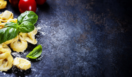 수 제 파스타 라비올리 밀가루, 토마토와 바 질 어두운 빈티지 배경에 상위 뷰