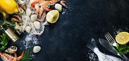 Delicious fresh fish and seafood on dark vintage background.  Banco de Imagens