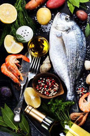 おいしい新鮮な魚やシーフード暗いビンテージ背景に。
